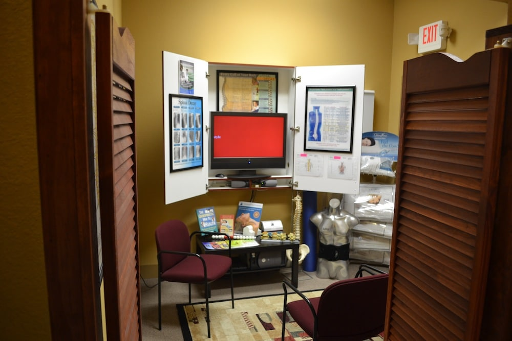 Image of One of the Treatment Rooms at Freedom Health Centers of McKinney Texas Showing Pillows, Medical Diagrams, Monitor, Plastic Spine