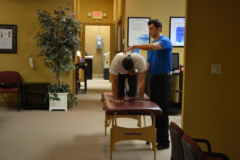 Image of one of the Staff at Freedom Health Centers of McKinney Texas Doing Physical Therapy on a Male Patient Who is on a Treatment Table