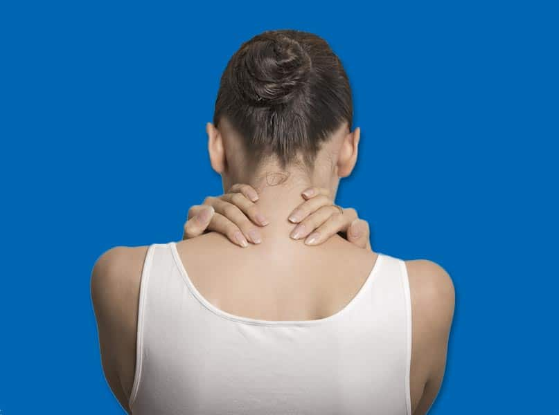Image of Back of Woman with Her Head Down and Her Hands Clutching the Back of Her Neck in Pain Due to Fibromyalgia - Freedom Health Centers