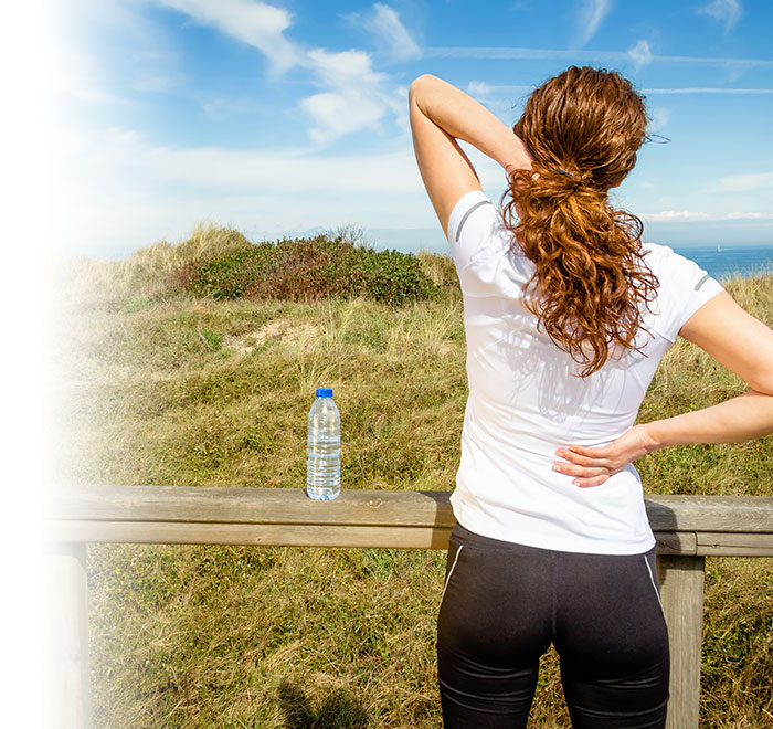 Image of Back of Woman Standing Outdoors with Her Hands on the Back of Her Neck and Back Due to Neck Pain and Back Pain - Freedom Health Centers - McKinney Chiropractor
